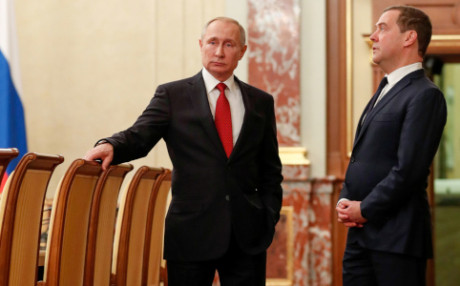 Russian President Putin and Prime Minister Medvedev speak before a meeting with government members in Moscow